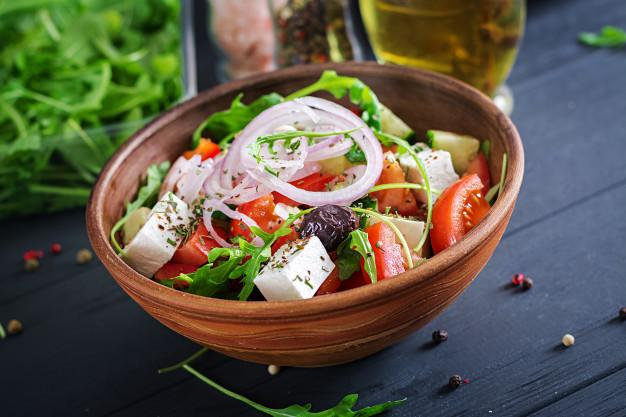 Greek salad with fresh tomato, cucumber, red onion, basil, feta cheese, black olives and italian herbs Free Photo