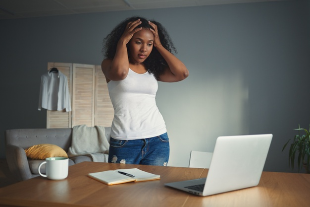 woman looking overwhelmed in front of her laptop