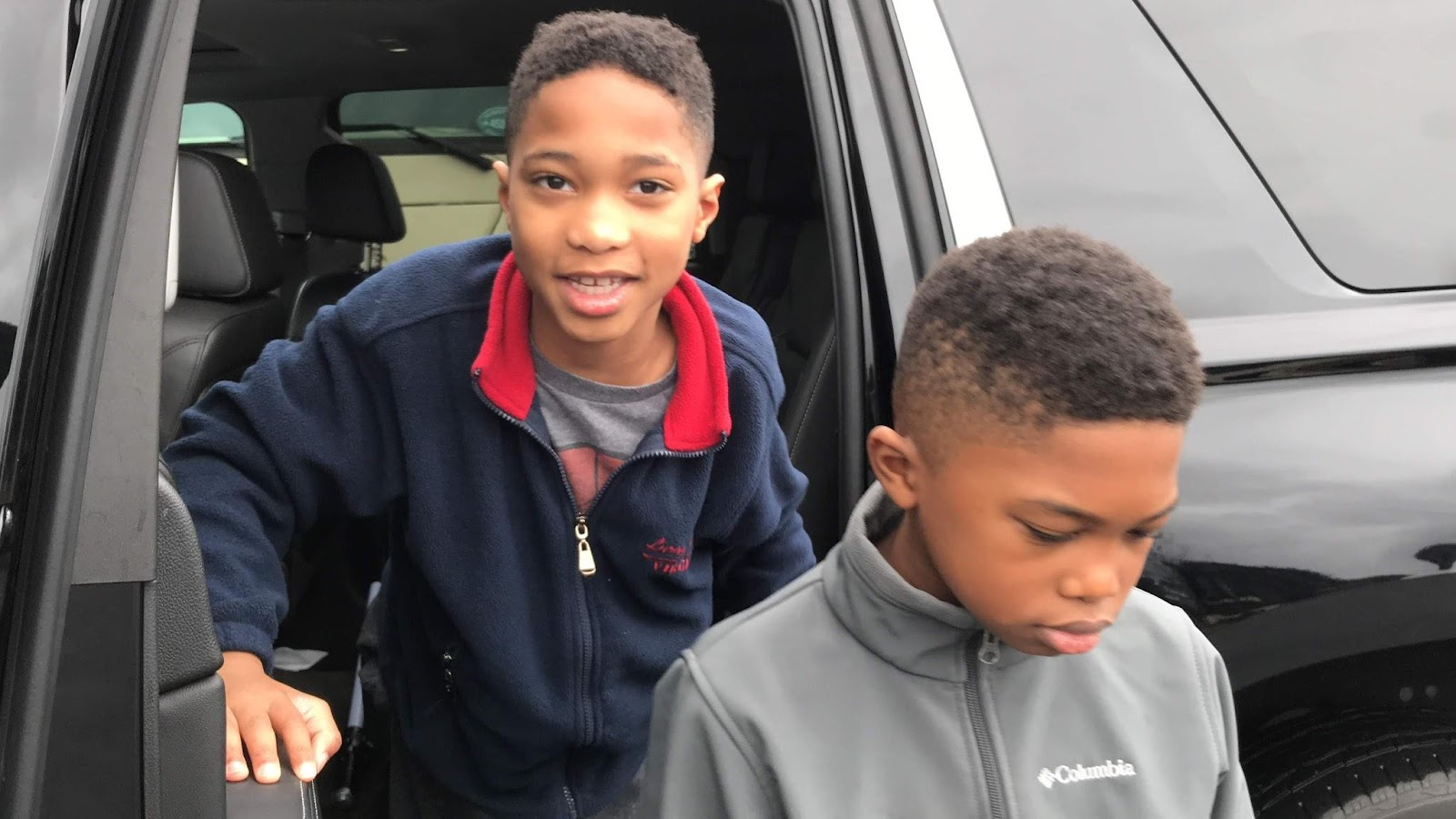 Two young boys exiting a car