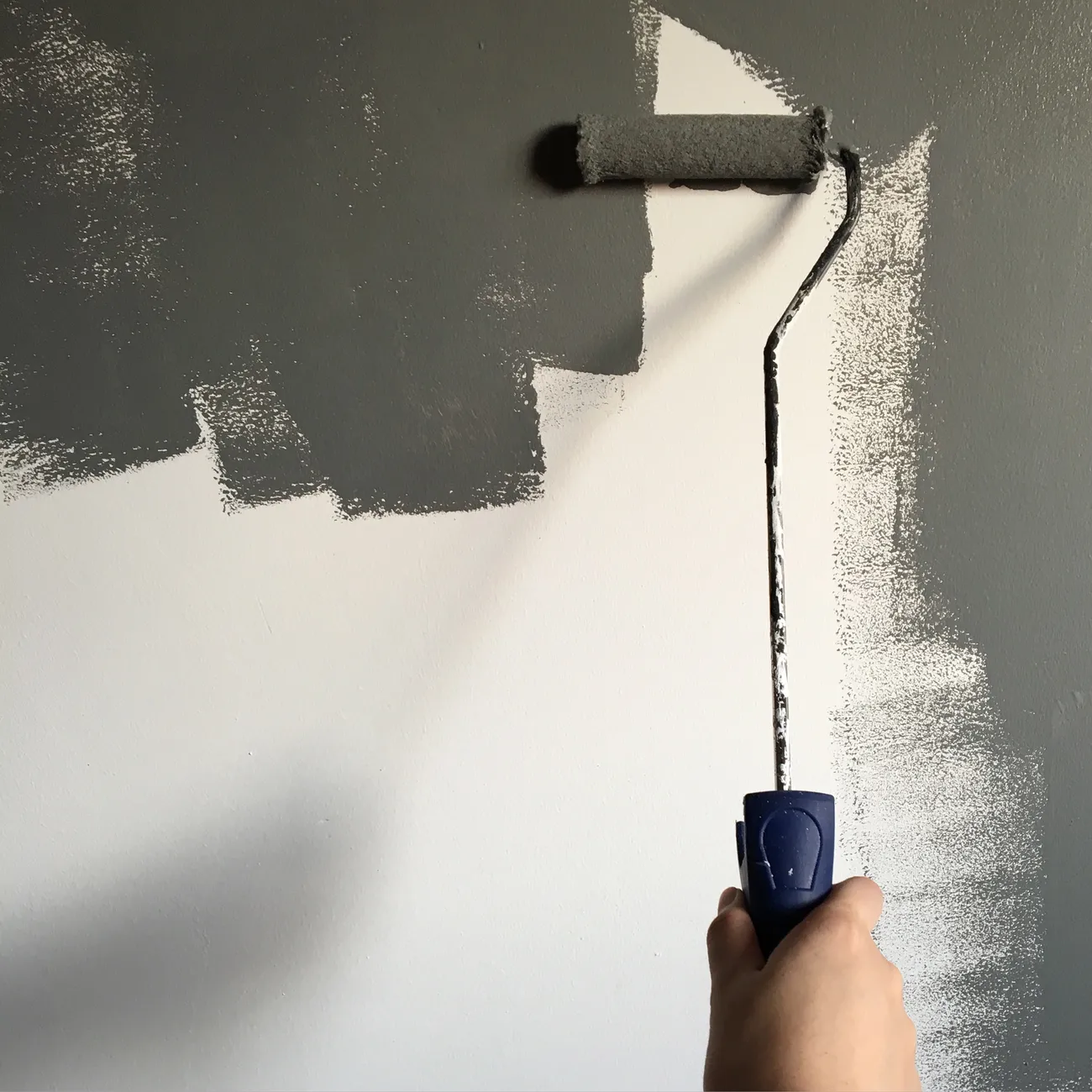 roller paint brush painting a white wall gray