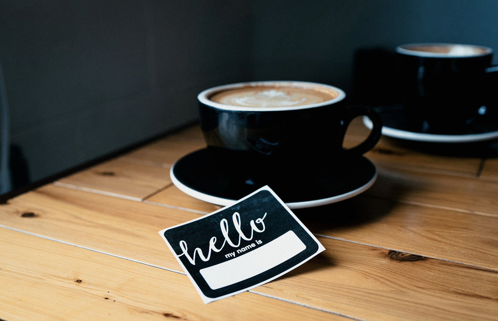 A coffee cup on a table with a 'hello my name is' sticker set next to it