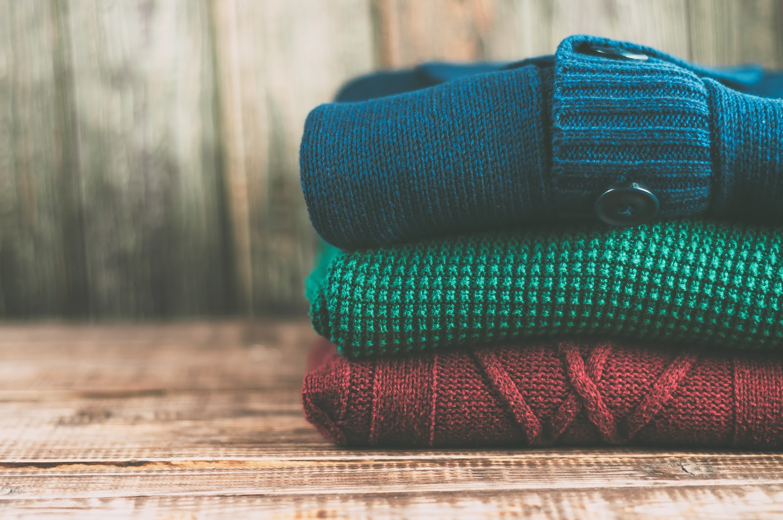 A stack of colorful fall sweaters