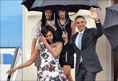 美國總統歐巴馬抵達古巴展開歷史性訪問,圖為歐巴馬偕同夫人蜜雪兒及兩個女兒步下專機,歐巴馬揮手致意,笑容滿面。 (法新社)