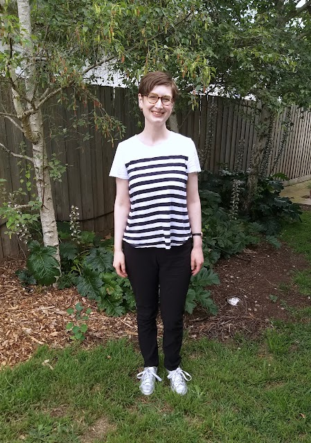 Siobhan stands in front of a garden fence. She wears slim fit black pants with hard-to-notice front pockets, striped white and navy short sleeve tee and silver runners.
