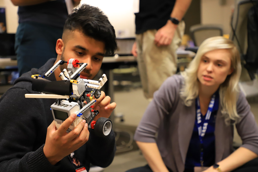 A young blonde female looks on as a male peer inspects a robotics project.