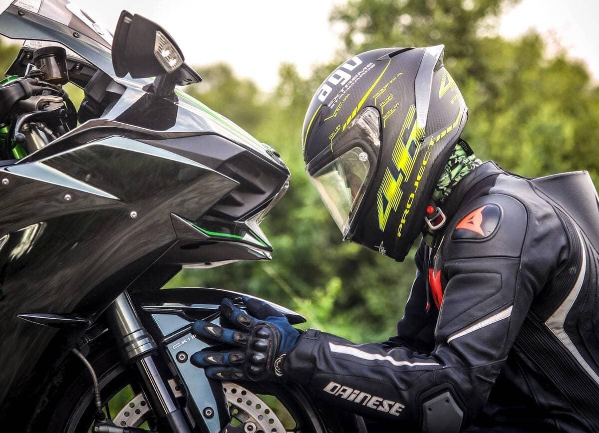 Un motociclista a fianco della sua moto nera