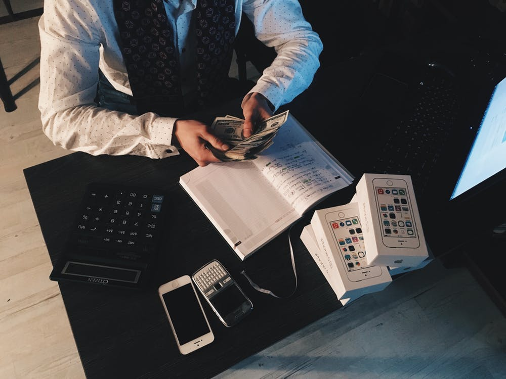 Person Counting Money With Smartphones in Front on Desk how to save money