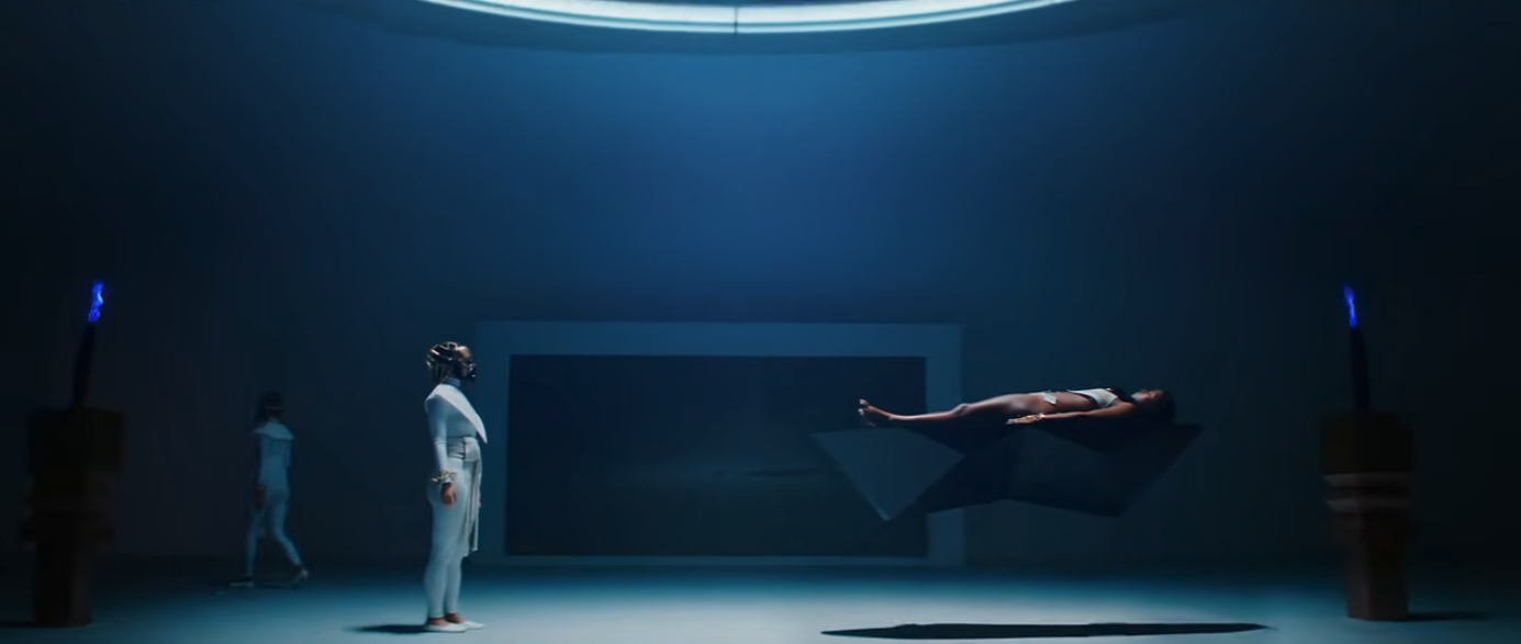 A wide shot of a dark room lit from above. On one side, Jane is wearing a bikini and on a floating table. On the other side Zen is wearing a white ceremonial leotard outfit and gold mask.