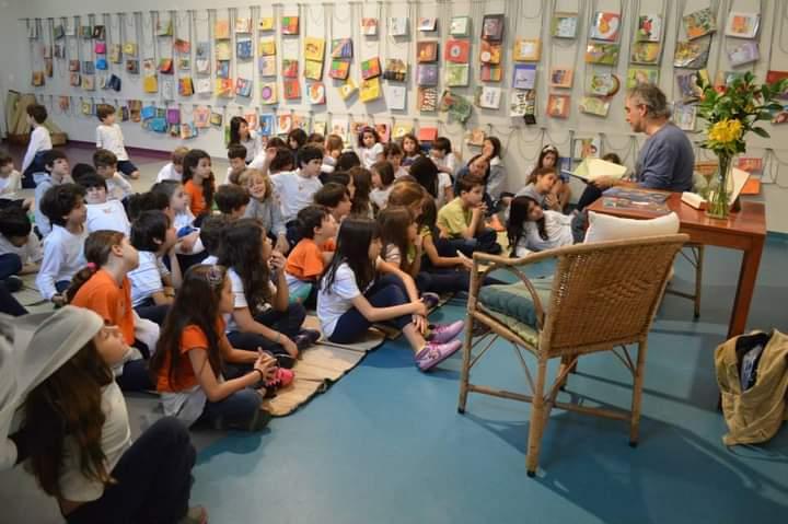 A imagem mostra um adulto lendo um livro para uma plateia de crianças.