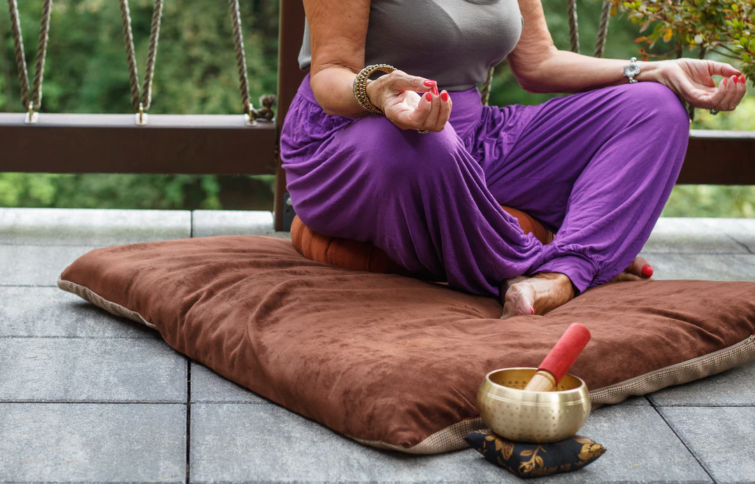Woman sitting on a brown cushion and meditating