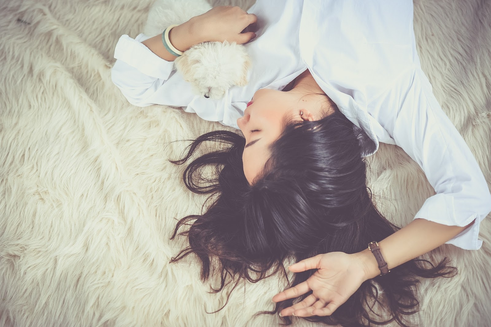 A girl lying down asleep while cuddling her dog