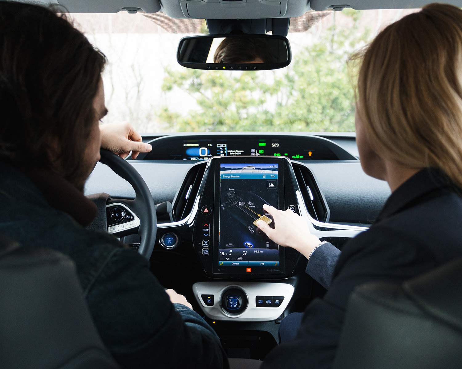 Two people navigate through Toyota's Entune system on a large touchscreen display