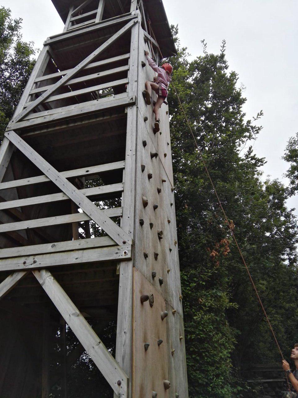 Niña subiendo el rocódromo durante la actividad multiaventura de escalada en el campamento de verano Emosie Camp Fest
