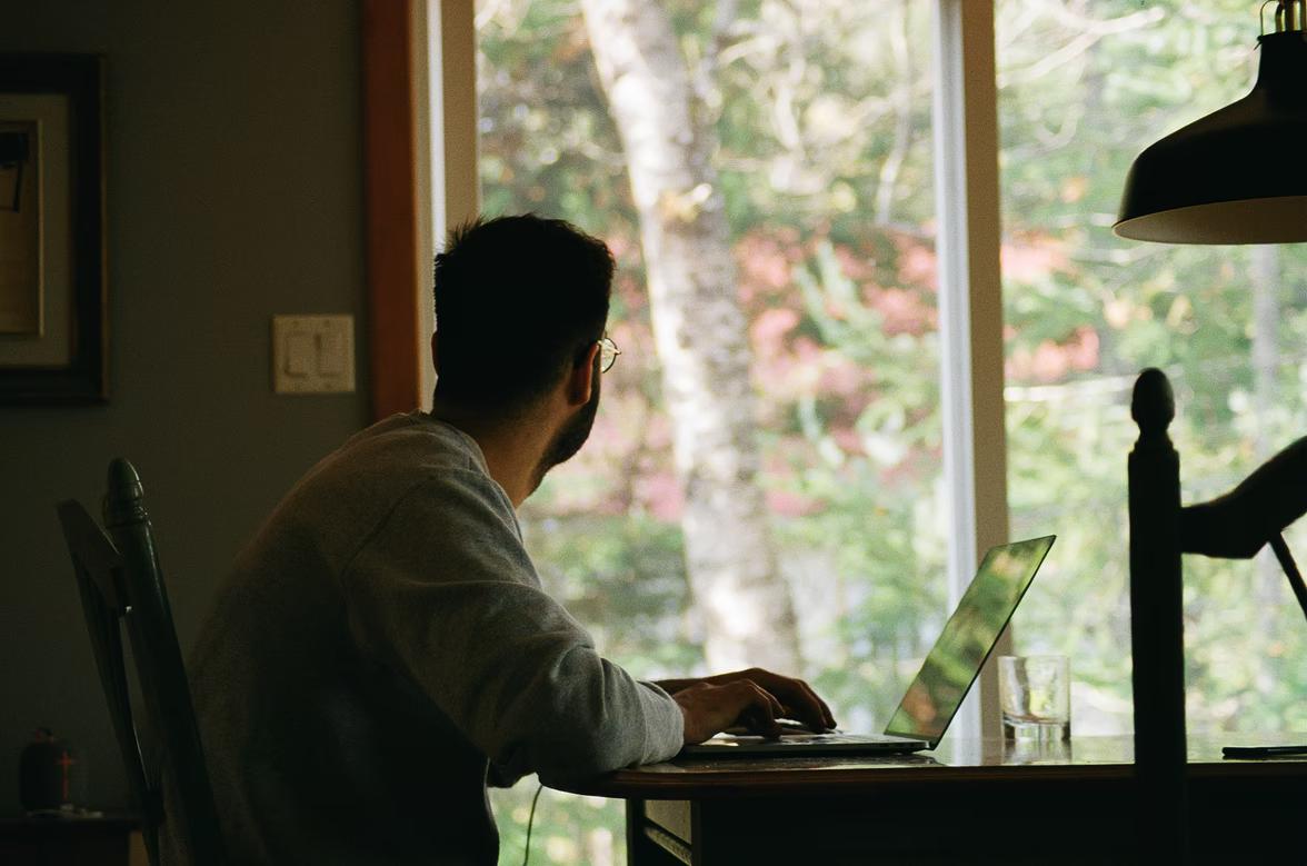 muž pracujúci za notebookom hľadí cez veľké okno smerom do lesa