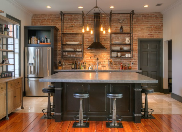 modern industrial kitchen with oversized center island. featuring stainless steel bar stools and cement countertop
