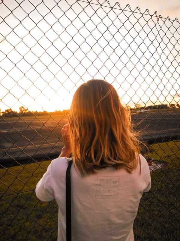 Foto de uma menina de costas olhando para o por-do-sol