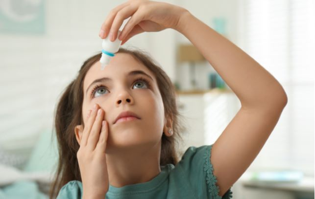Young girl putting in eye drops into eye while looking up