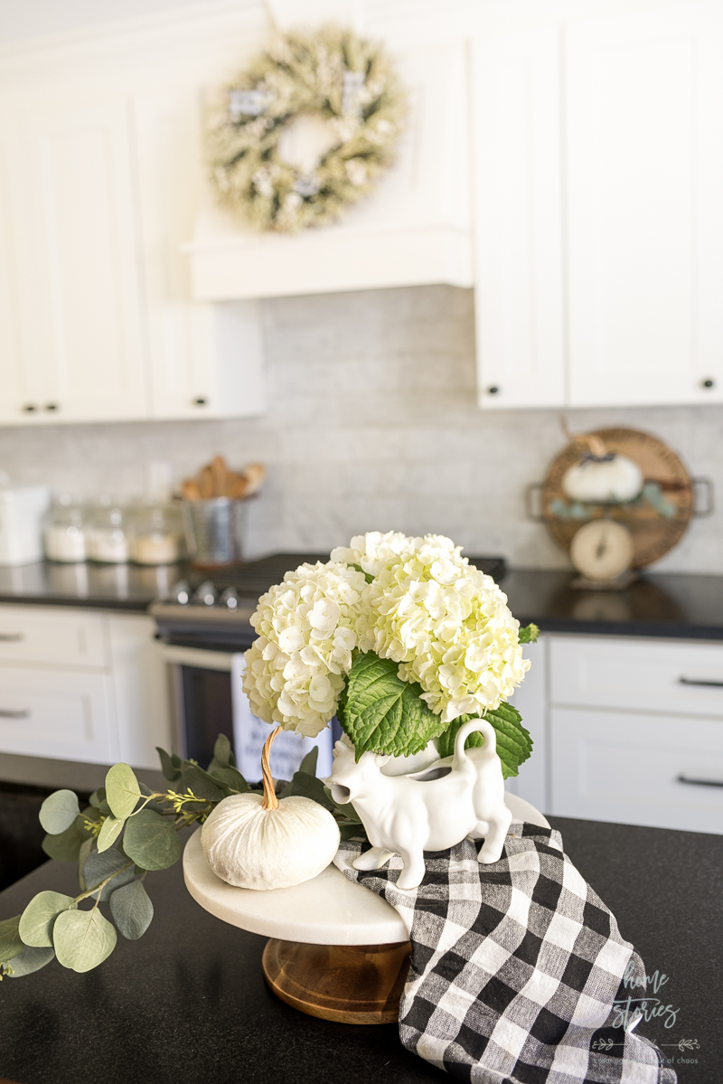 black kitchen countertop with white cabinets featuring small tray. tray holds a small white pumpkin, fresh white flowers, black and white checkered kitchen towel