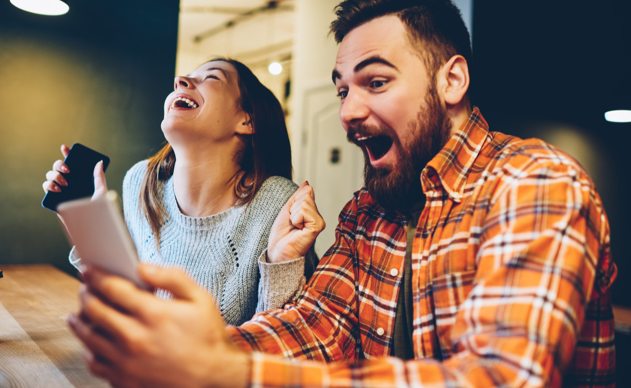 Excited male and female rejoice in winning an internet lottery on smartphone