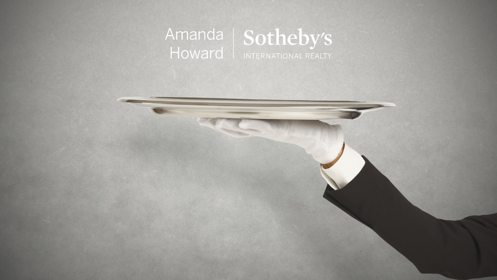 White Glove holding a tray with the Amanda Howard Sotheby's International logo on gray background