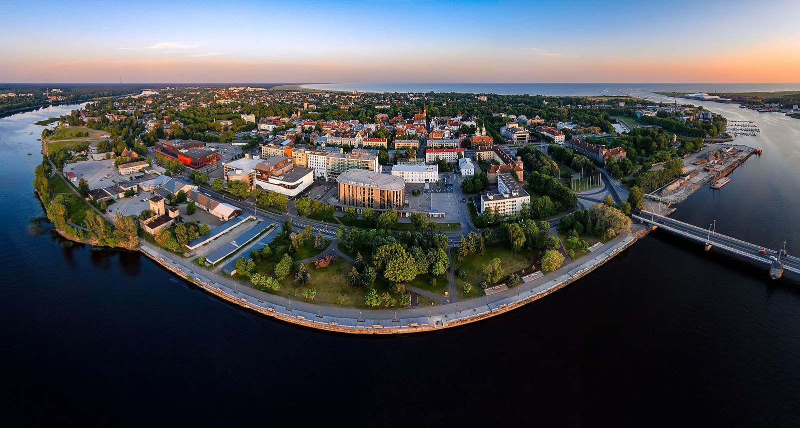 aerial view of parnu. waterfront buildings and parks, bridge connecting to mainland. sunset in estonia.