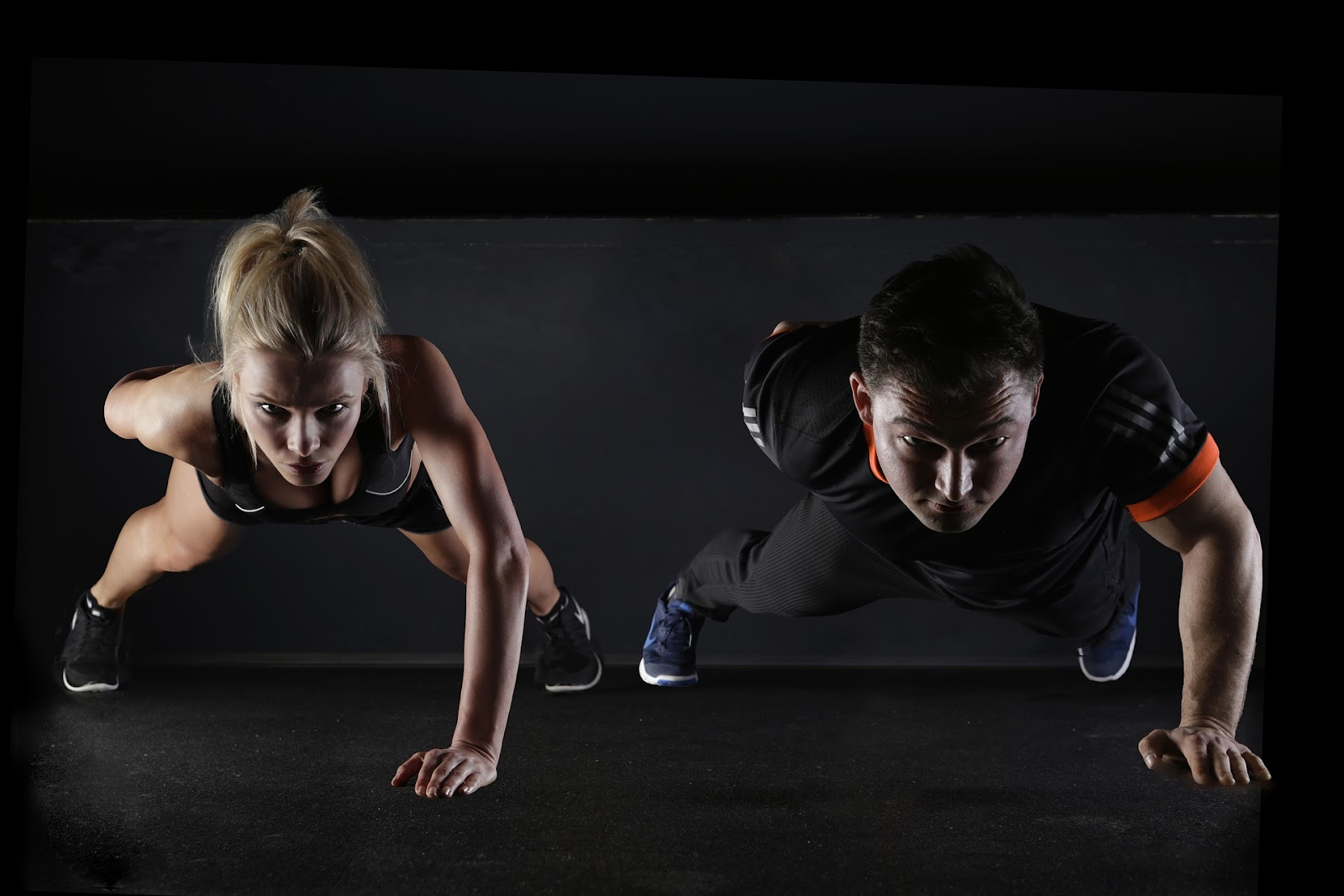 a man and a woman doing one-armed push-ups