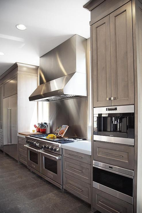 kitchen with grey washed shaker cabinets, dark tile floors, stainless steel appliances and large range hood