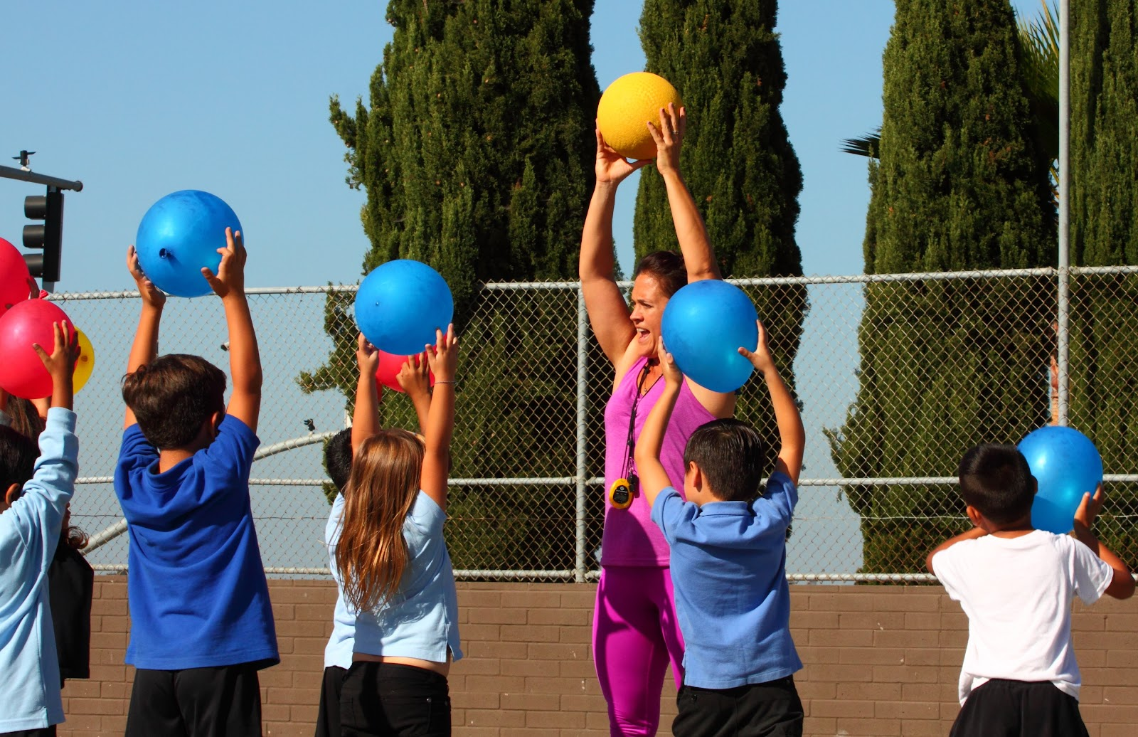 Empower Language Academy coach holds a ball in the air and leads five students in a CrossFit Kids activity