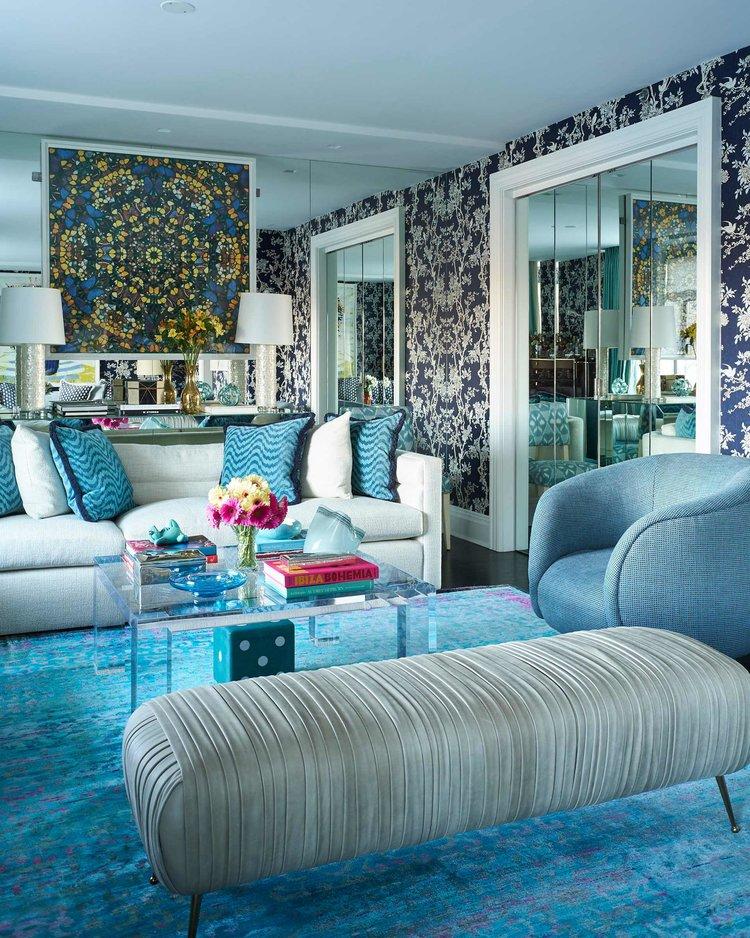 Sala com papel de parede floral, tapete azul, poltrona azul, sofá branco e almofadas.
