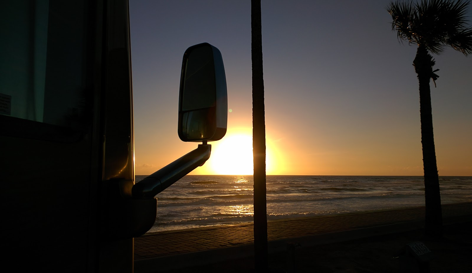 Class A RV parked at the beach during sunset