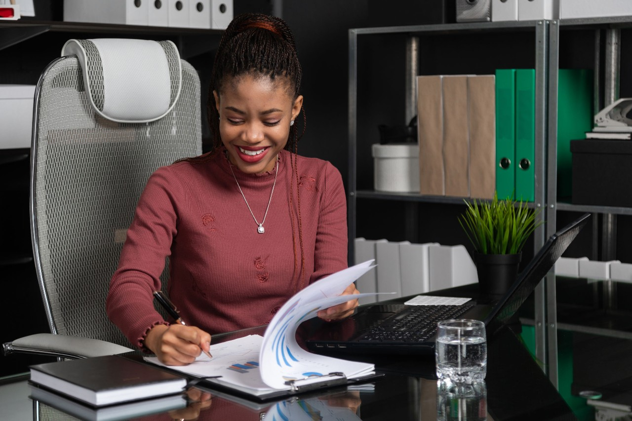 smiling woman at desk looking at paper charts and her computer; EDC features concept