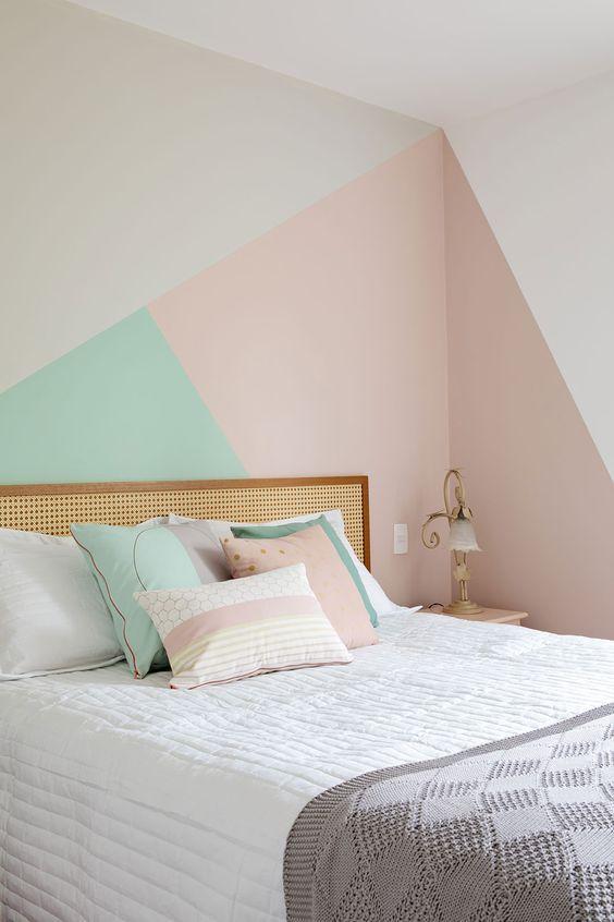Quarto de casal com parede da cabeceira com pintura geométrica.