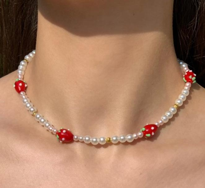 A necklace on a person's chest  Description automatically generated with medium confidence
