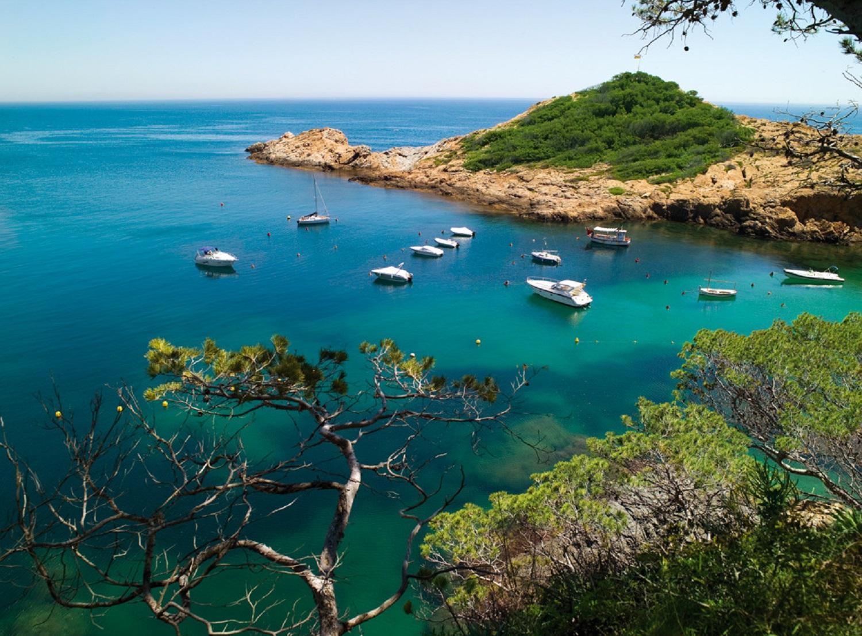 Cala Sa Tuna con barcos atracados y aguas cristalinas
