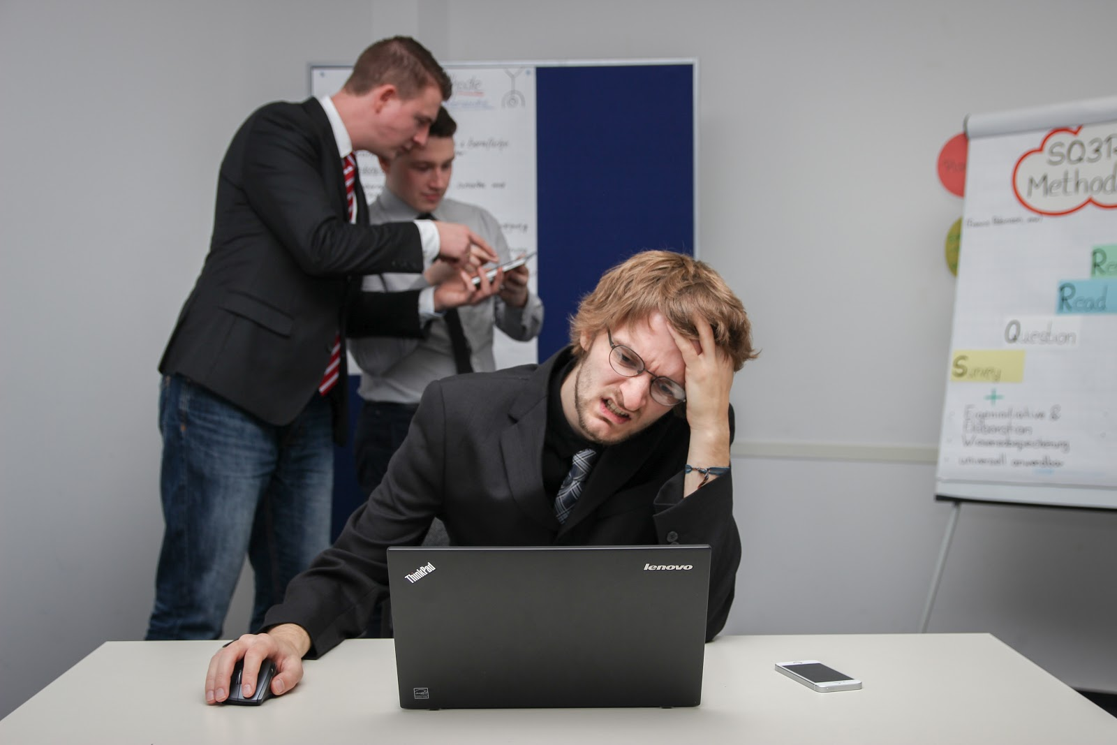 employee stressed in front of laptop, colleagues in background