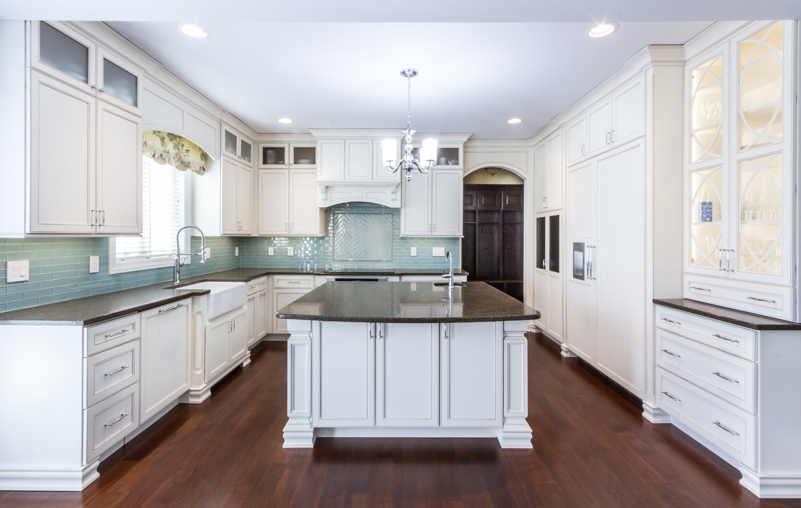 White kitchen with dark countertops and seafood polished glass  tile backsplash. Detailed glass cabinet fronts and arched entry warty with lots of natural light.