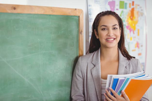 Professora segurando cadernos sobre formação continuada em frente a uma lousa.