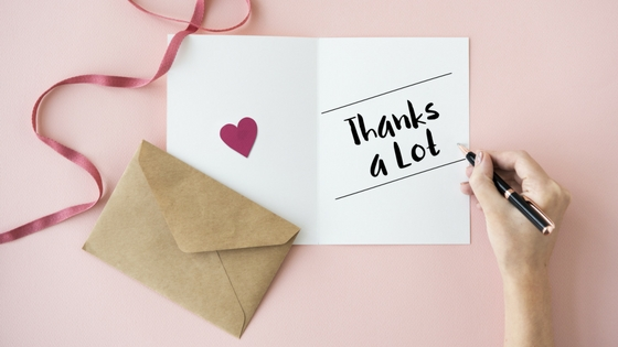 A thank you card displaying a heart, a pink ribbon, and an envelope on a light pink background