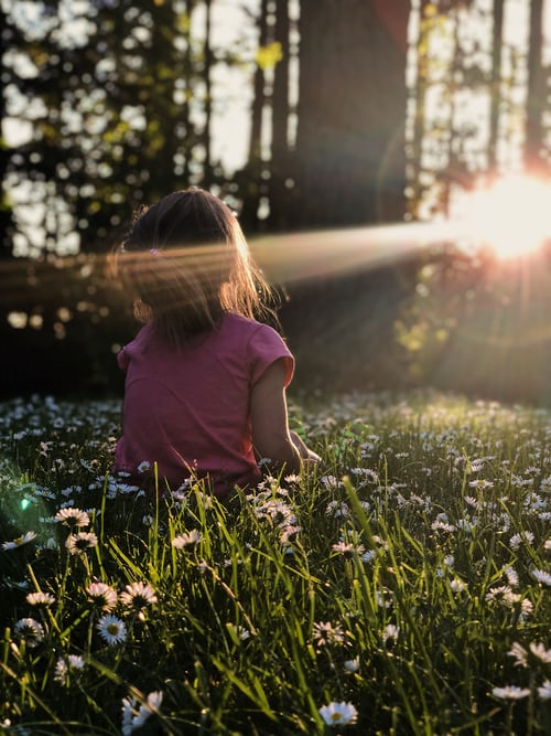 Young girl sat in daisy meadow