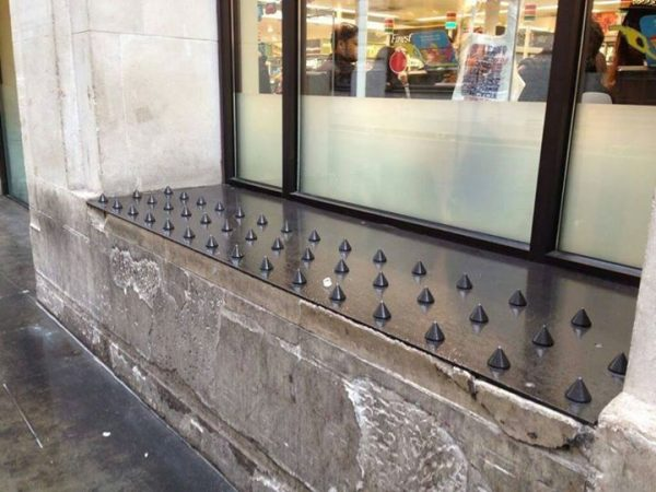 The ledge in front of a store window is covered in metal spikes intended to keep homeless people from sitting or sleeping there.