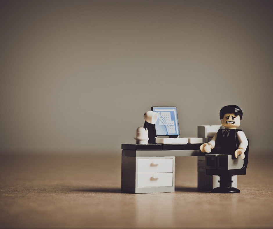 Lego people pleasing worker in brown vest and khaki pants sitting at a desk in an empty room with a face of chagrin.