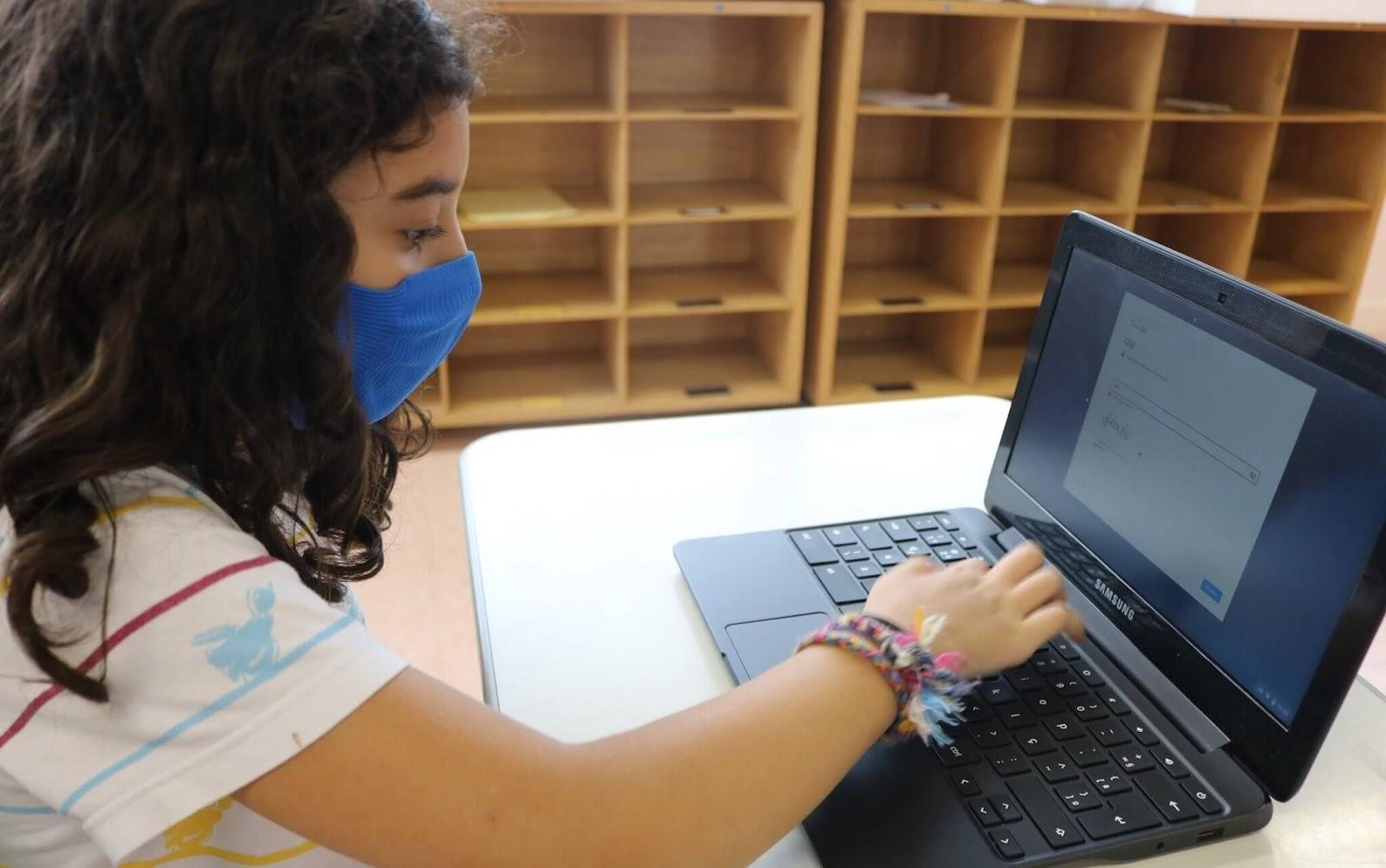 A imagem mostra uma aluna com máscara em atividade on-line.