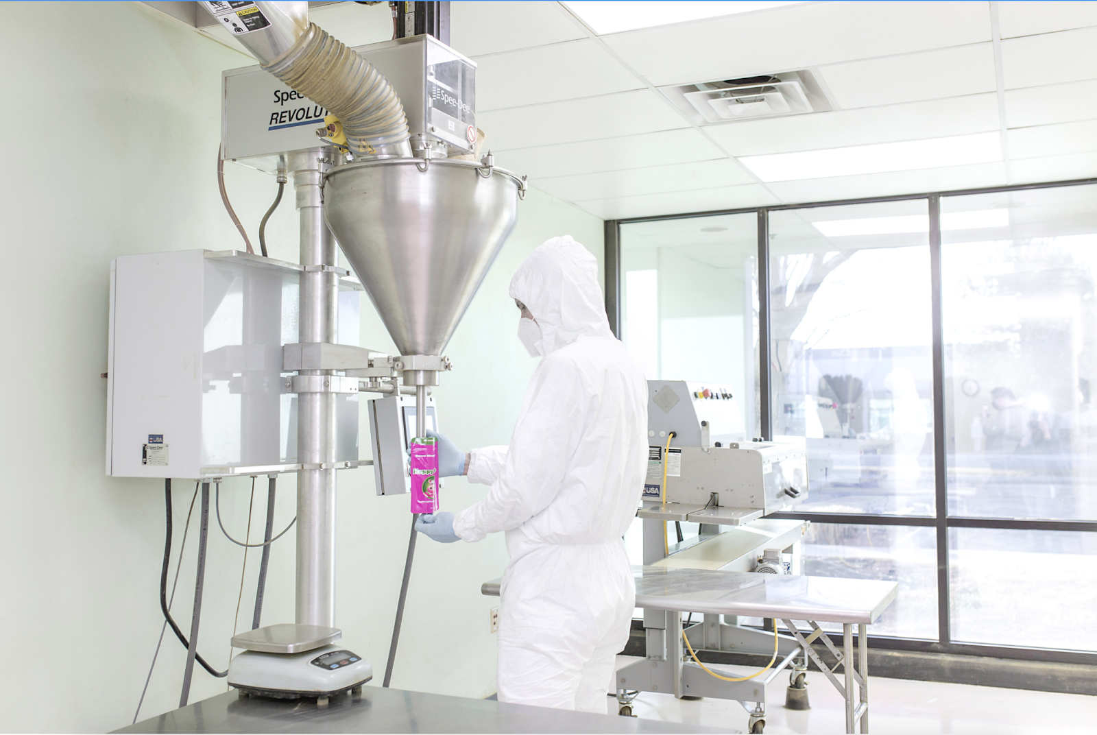 Image of a Happy Hippo Herbals production lab working filling a packet of kratom powder