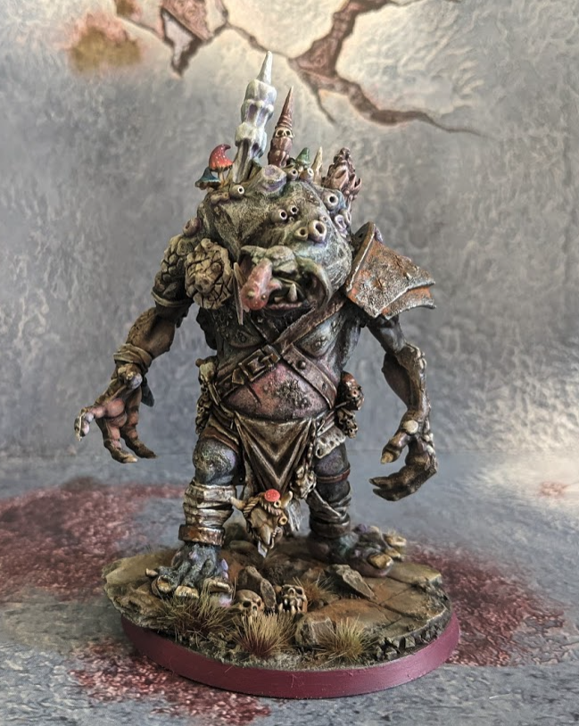 Model of a Troll, with large clawed hands, heavy metal armour, and rocky outcroppings and growths growing out of its back and shoulders