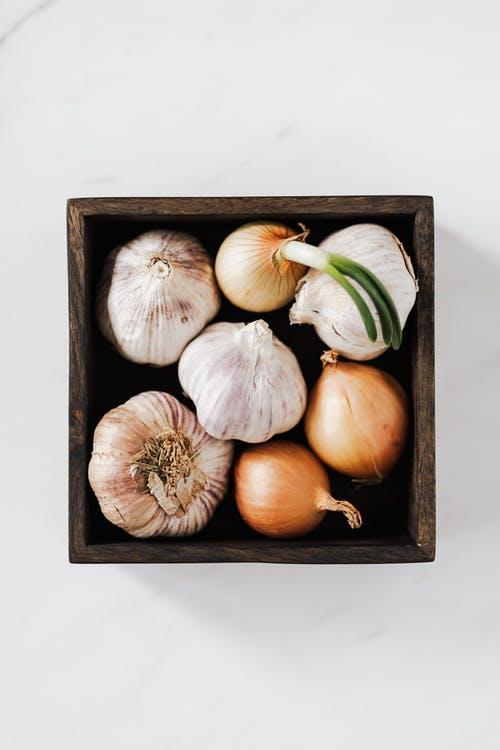 Onions and garlic heads in wooden box on table