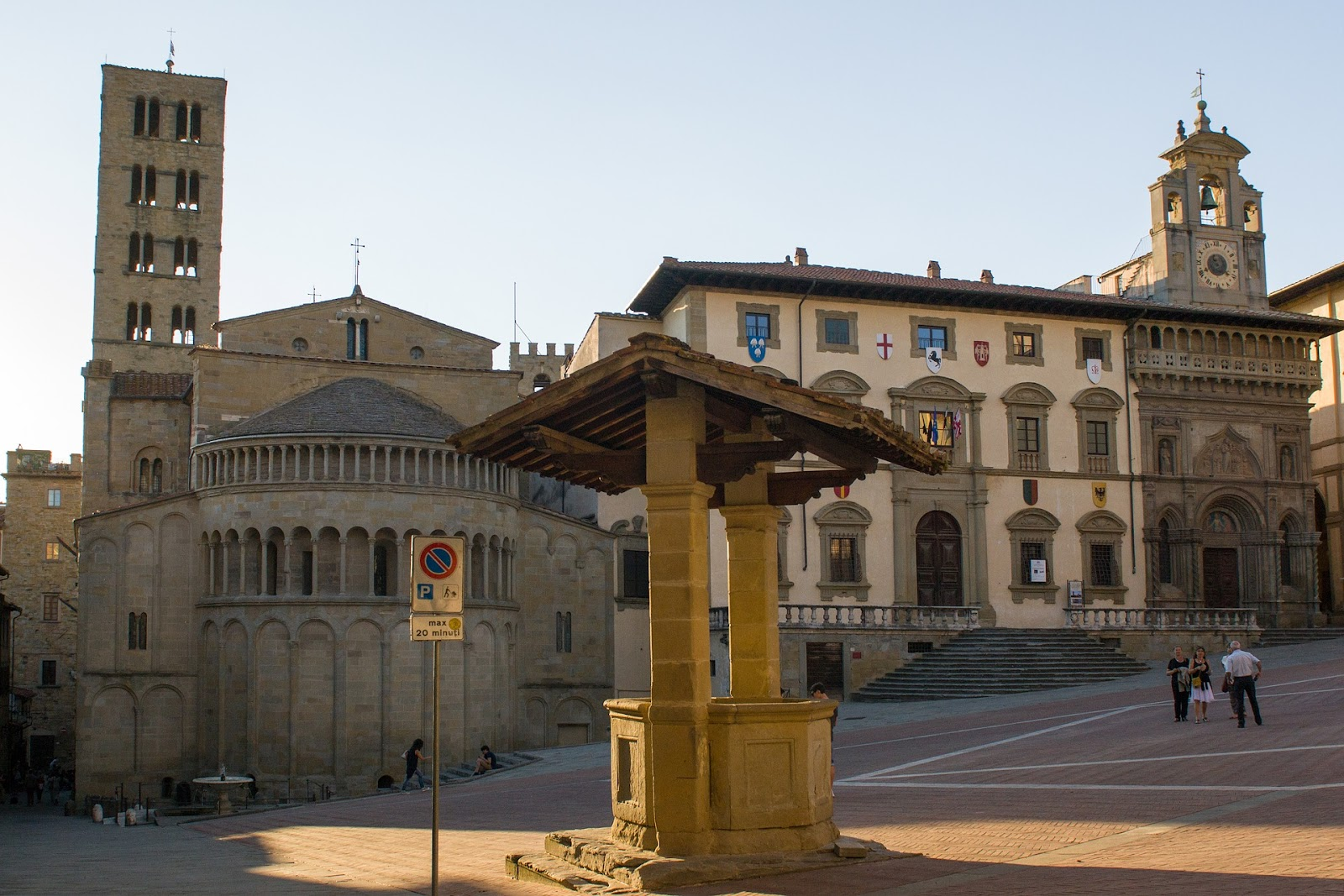 empty piazza grande main square in italy well in foreground and medieval  buildings in background during sunrise in arezzo italy