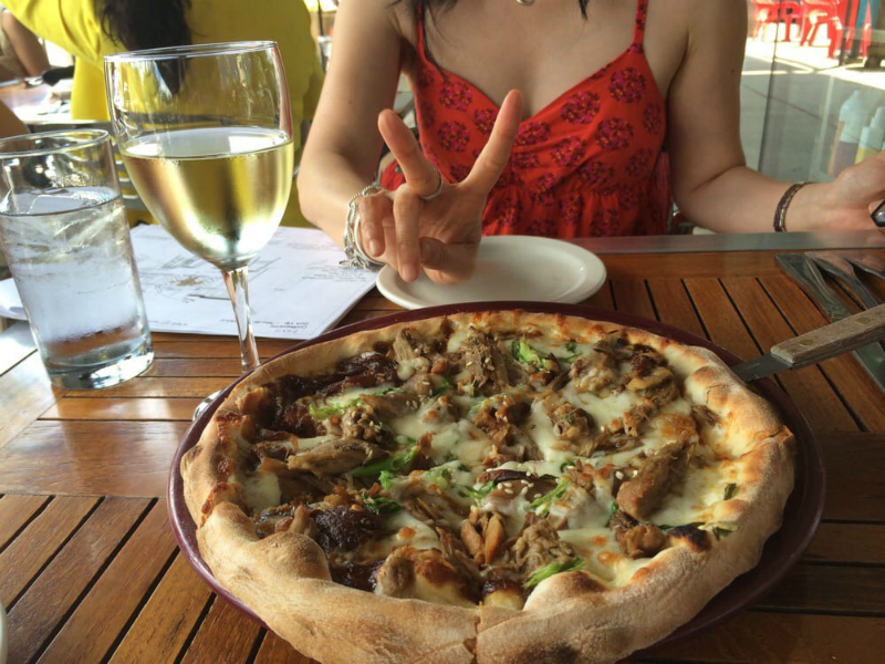 A woman at a table with wine and pizza at SPAGIO