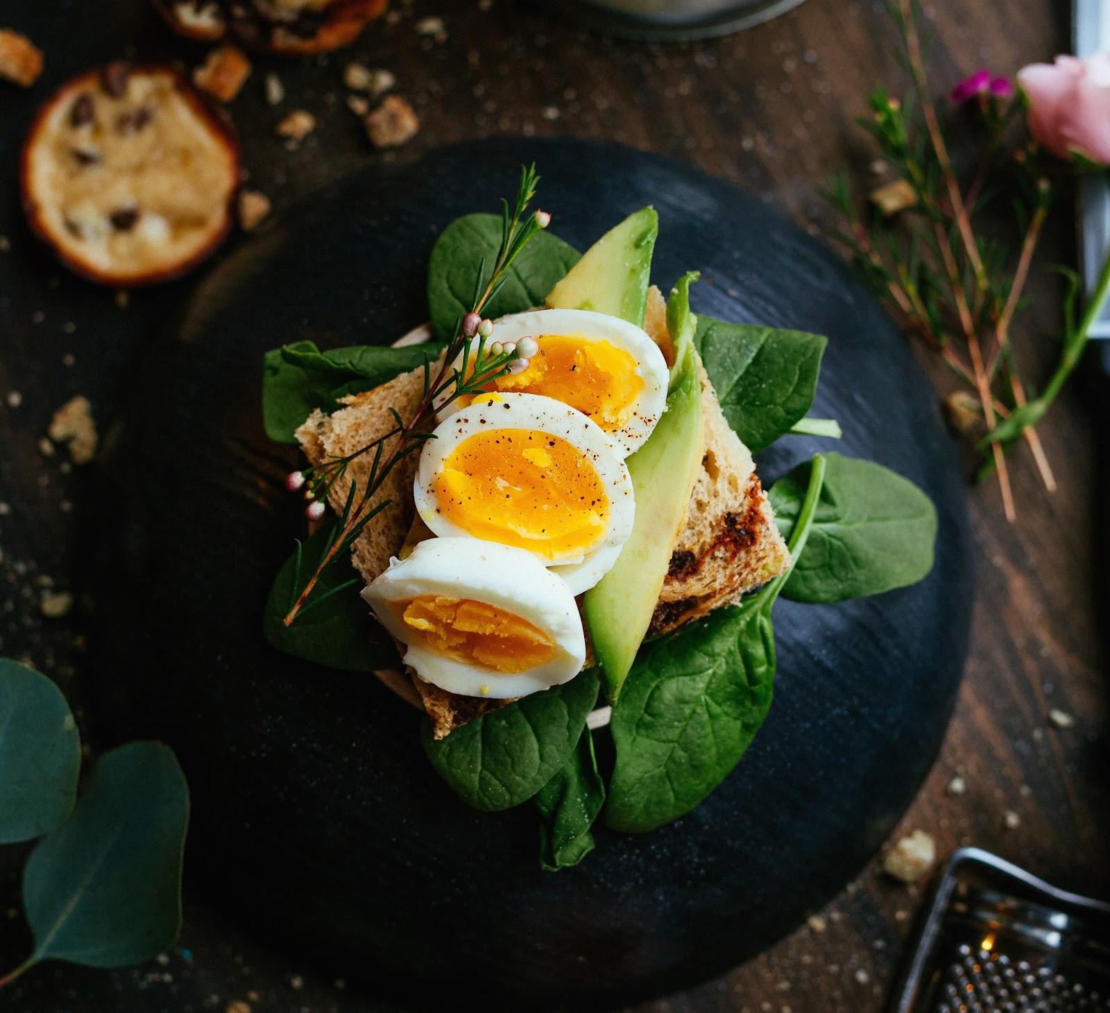 Sliced boiled egg on avocado toast.