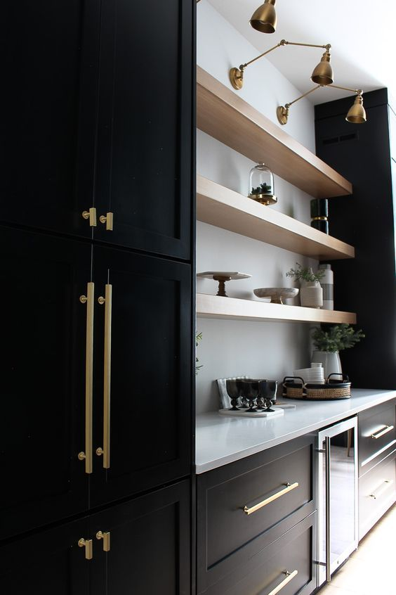 black shaker cabinets with white walls, open wood shelving and brass accents