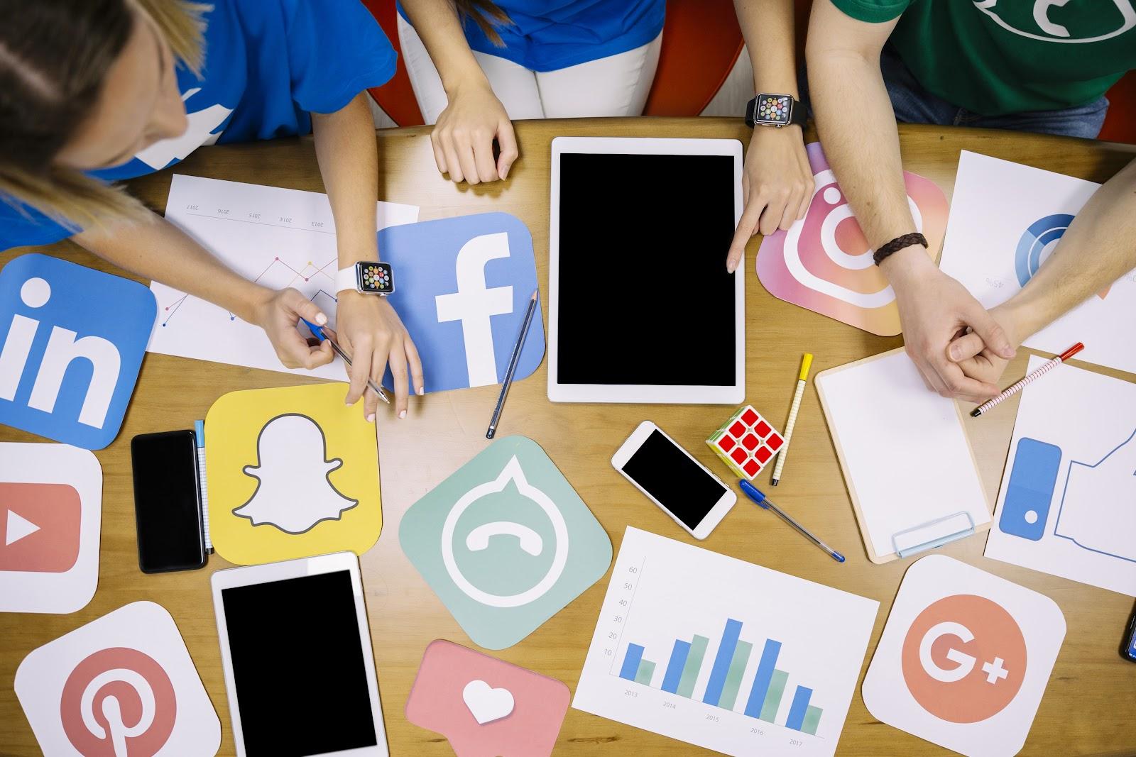 Pessoas jovens debruçam em mesa de trabalho com ícones de redes sociais